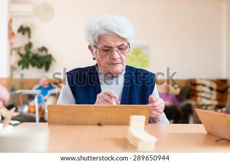 Eldelrywoman playing rummy - stock photo