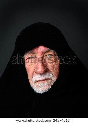 Elder Arab Sheik with a somber expression with a black headdress looking directly into the camera - stock photo