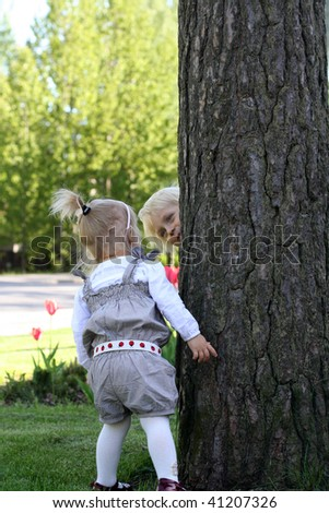 Elder brother is hiding behind a tree .But cute little sister found him. - stock photo