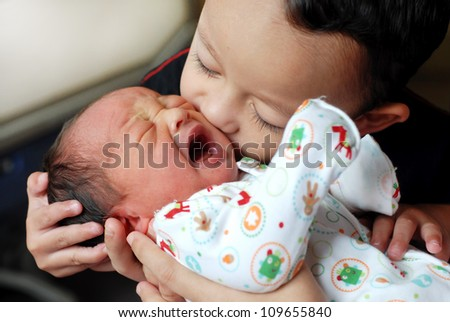 Elder brother kisses in a cheek junior brother - stock photo