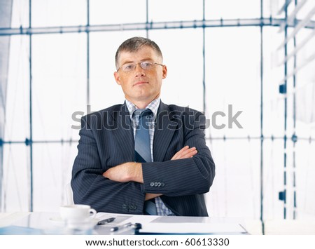 Elder businessman smiling and sitting at his office
