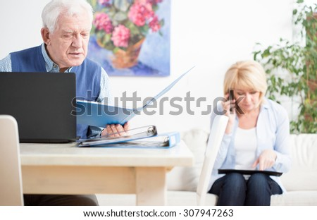 Elder businesspeople checking important docuemnts of their company