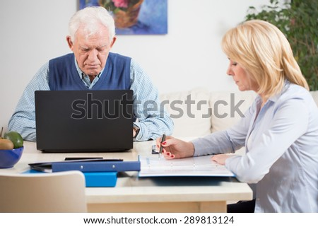 Elder couple working in their home office - stock photo