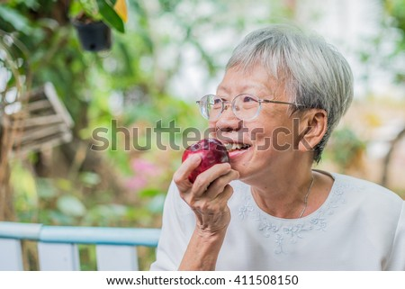 elder eating apple