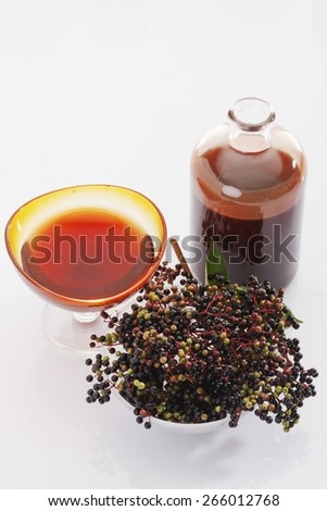 Elder, elderberries, glass bowl with elderberry juice, bottle - stock photo