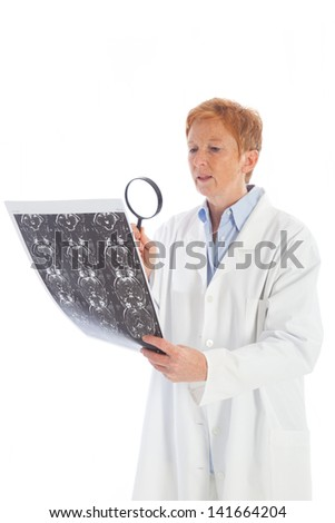 elder female doctor in a white lab coat viewing a magnetic resonance tomography print of a skull and holding a magnifying glass - stock photo
