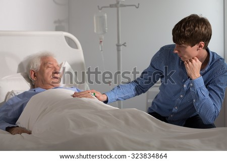 Elder ill man sleeping and a relative holding his hand - stock photo