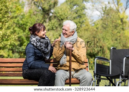 Elder man and carer in the park - stock photo