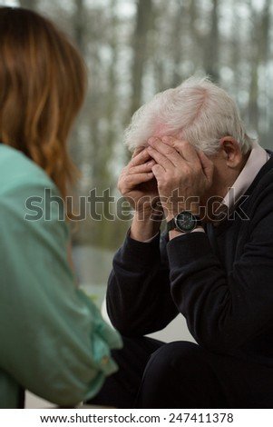 Elder man crying during visit in psychiatrist - stock photo