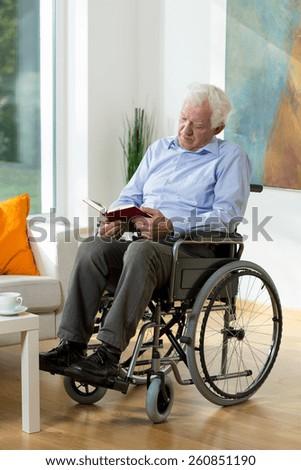 Elder man in a wheelchair reading a book - stock photo