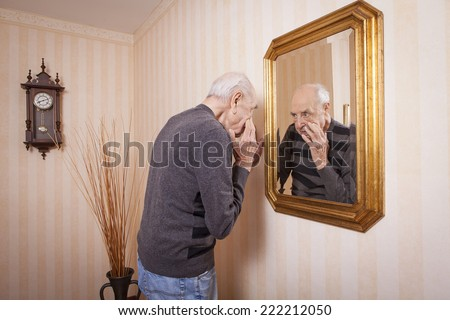 elder man looking at himself at the mirror - stock photo