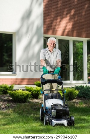 Elder man mowing grass in the garden