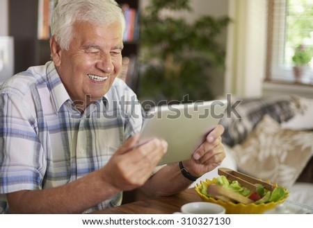 Elder man using a digital tablet at the table - stock photo