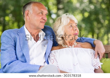 Elder marriage sitting on the bench in park