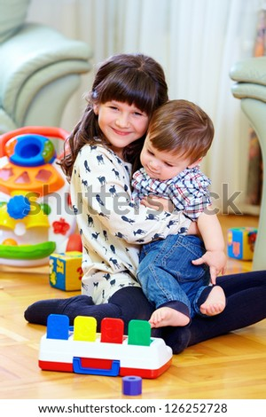 elder sister playing with little brother at home - stock photo
