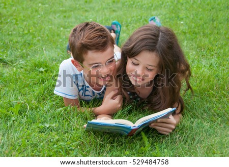 Elder sister reading a book for her brother