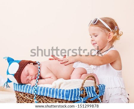 Elder sister taking care of a sleeping infant - stock photo