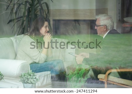 Elder therapist consulting young patient at home - stock photo