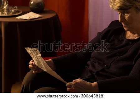 Elder woman calling old times to her mind - stock photo