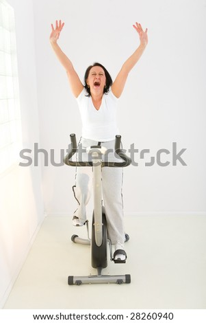 Elder woman exercising on bike. She's screaming and has raised hands. - stock photo