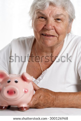Elder woman holding and hugging funny pink piggybank. Budgeting expenses, making savings, effective investment concept. Future needs deposit. Focus on pig. Retirement and retiree finansial problems - stock photo