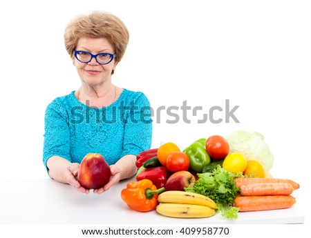 Elder woman holding red apple in hands, sitting with fresh fruit and vegetables on table, isolated on white background - stock photo