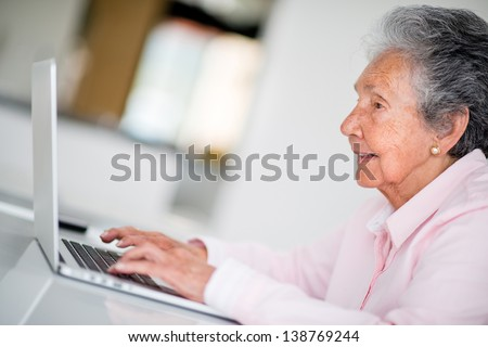 Elder woman using a computer and looking very happy - stock photo