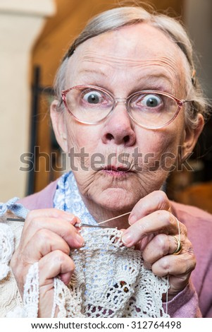 Elder woman with crochet and funny facial expression - stock photo