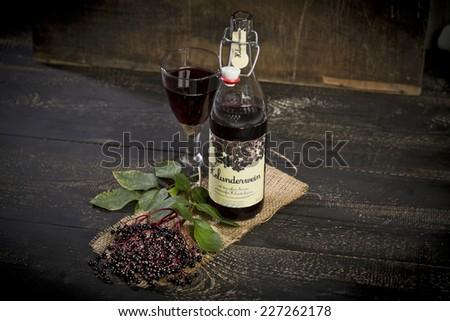 Elderberry wine and elderberries on wooden table - stock photo