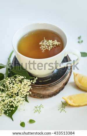Elderflower tea in a white cup on wooden tray with with a sprig of fresh flowers, leafs and lemon. White rustic background. - stock photo