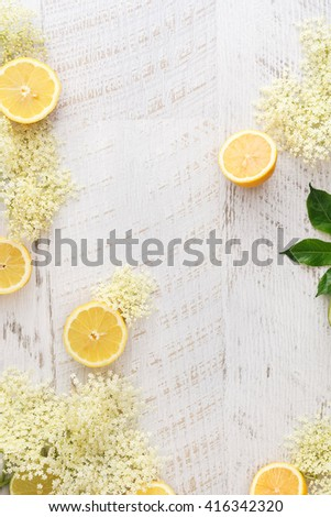 Elderflowers and lemons on a wooden surface.  Ingredients for elder flower syrup, rustic wood background. Top view, blank space - stock photo