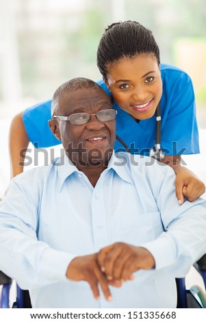 elderly african american man and caring young caregiver at home - stock photo