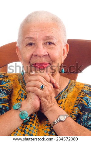 woman sitting in a chair clasping hands and smiling stock photo