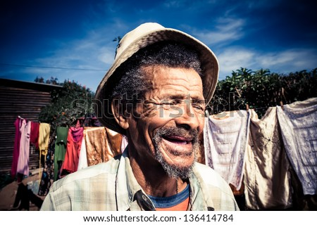 elderly african man in a old khaki hat laughing out loud - stock photo