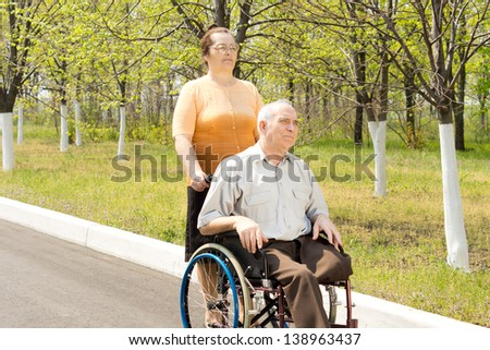 Elderly amputee with one leg amputated above the knee being taken for a walk in a wheelchair by his wife or carer
