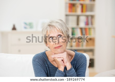 Elderly attractive woman sitting on a sofa in the living room reminiscing looking up into the air with a wistful expression - stock photo