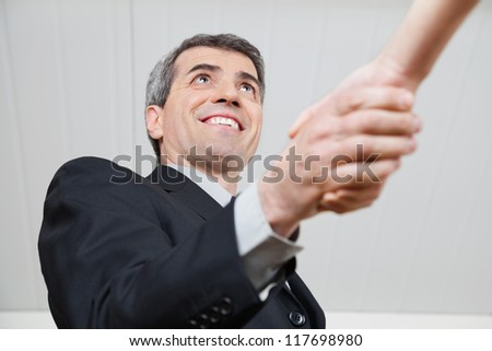 Elderly businessman giving businesswoman a handshake in the office - stock photo