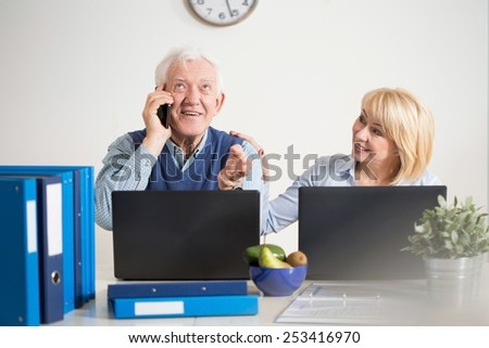 Elderly businessman talking on the phone with client - stock photo