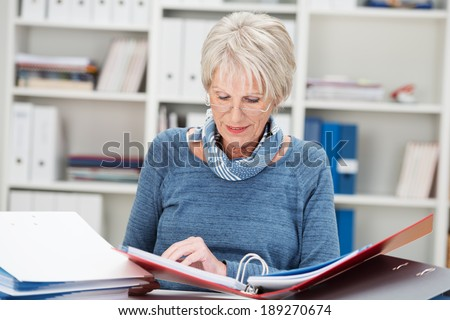 Elderly businesswoman hard at work at the office sitting at her desk reading from a business binder - stock photo