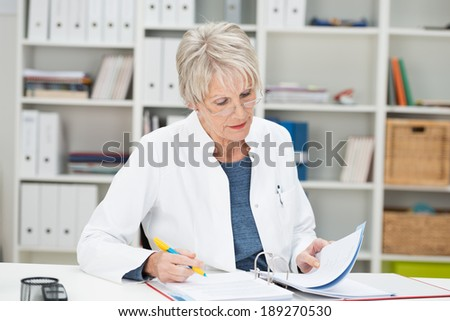 Elderly businesswoman working at her desk at the office reading through notes in a binder - stock photo