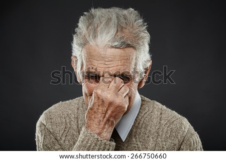 Elderly caucasian man with a strong migraine isolated on white