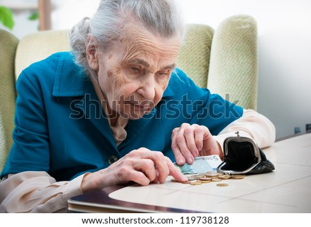 elderly caucasian woman counting money  on table - stock photo
