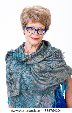 Elderly Caucasian woman portrait, blue spectacles, standing wrapped in shawl, white background - stock photo
