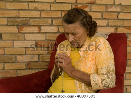 elderly caucasian woman with hands folded in prayer - stock photo