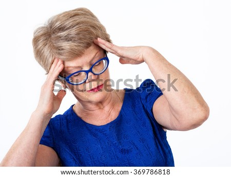 Elderly Caucasian woman with temporal headache, holding her head with hands, white background - stock photo