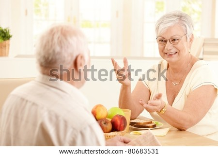 Elderly cheerful wife chatting to husband at breakfast table, gesturing, smiling.? - stock photo