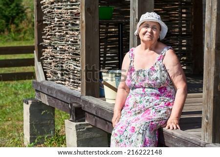 Elderly cheerful woman sitting near own house - stock photo