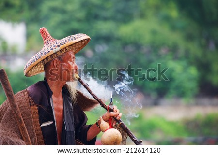 Elderly Chinese fisherman in traditional clothes smoke cigaret. - stock photo