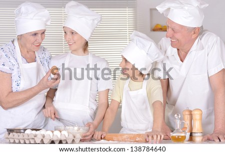 elderly couple and their grandchildren kneading the dough for the cake together - stock photo