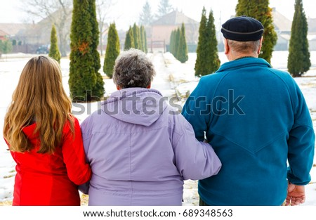 Elderly couple and young caregiver walking in the park in wintertime